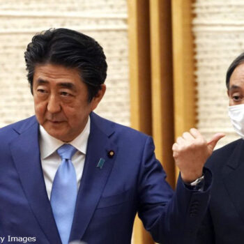 Shinzo Abe, Japan's prime minister, left, gestures towards Yoshihide Suga, Japan's chief cabinet secretary, during a news conference in Tokyo, Japan, on Monday, May 4, 2020. Japan extended its nationwide state of emergency until May 31, with Abe saying the countrys coronavirus measures need more time to reduce infection rates. Photographer: Eugene Hoshiko/AP/Bloomberg via Getty Images