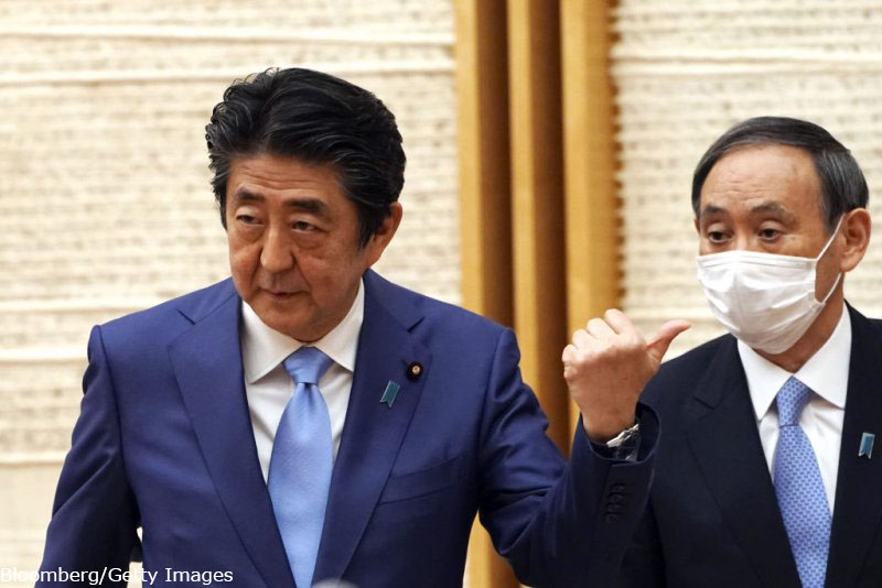 Shinzo Abe, Japan's prime minister, left, gestures towards Yoshihide Suga, Japan's chief cabinet secretary, during a news conference in Tokyo, Japan, on Monday, May 4, 2020. Japan extended its nationwide state of emergency until May 31, with Abesaying the countrys coronavirus measures need more time to reduce infection rates. Photographer: Eugene Hoshiko/AP/Bloomberg via Getty Images